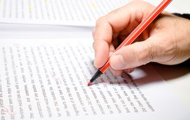 Man's hand correcting printed text with red pen