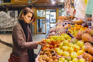 A woman chooses from different produce options at a market.
