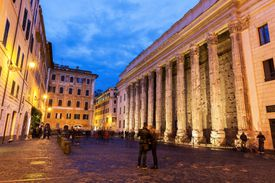 Couple standing in Piazza di Pietra in the evening