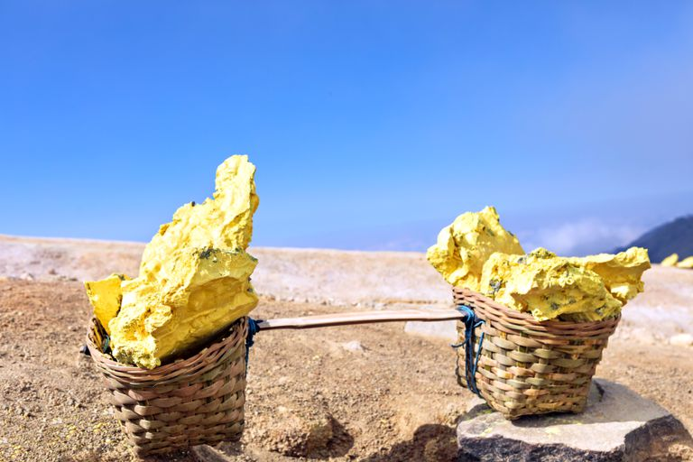 Baskets full of bright yellow sulfur mined from Kawah Ijen volcano in Indonesia