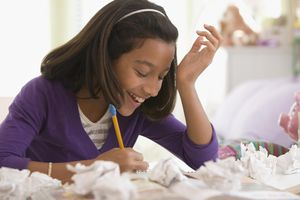 Girl writing an essay with a pencil surrounded by crumpled pieces of paper
