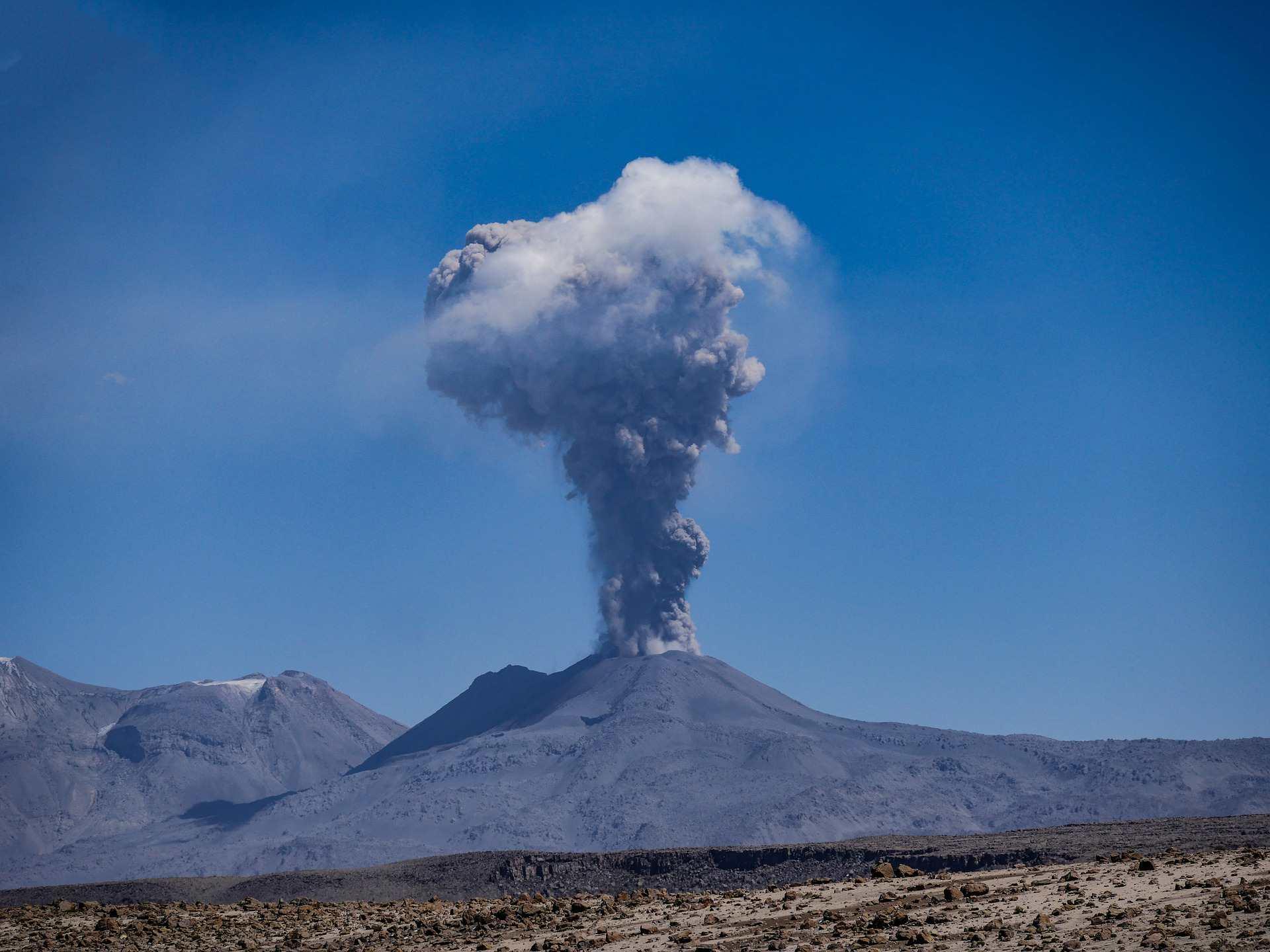 Volcano spewing smoke into a blue sky.