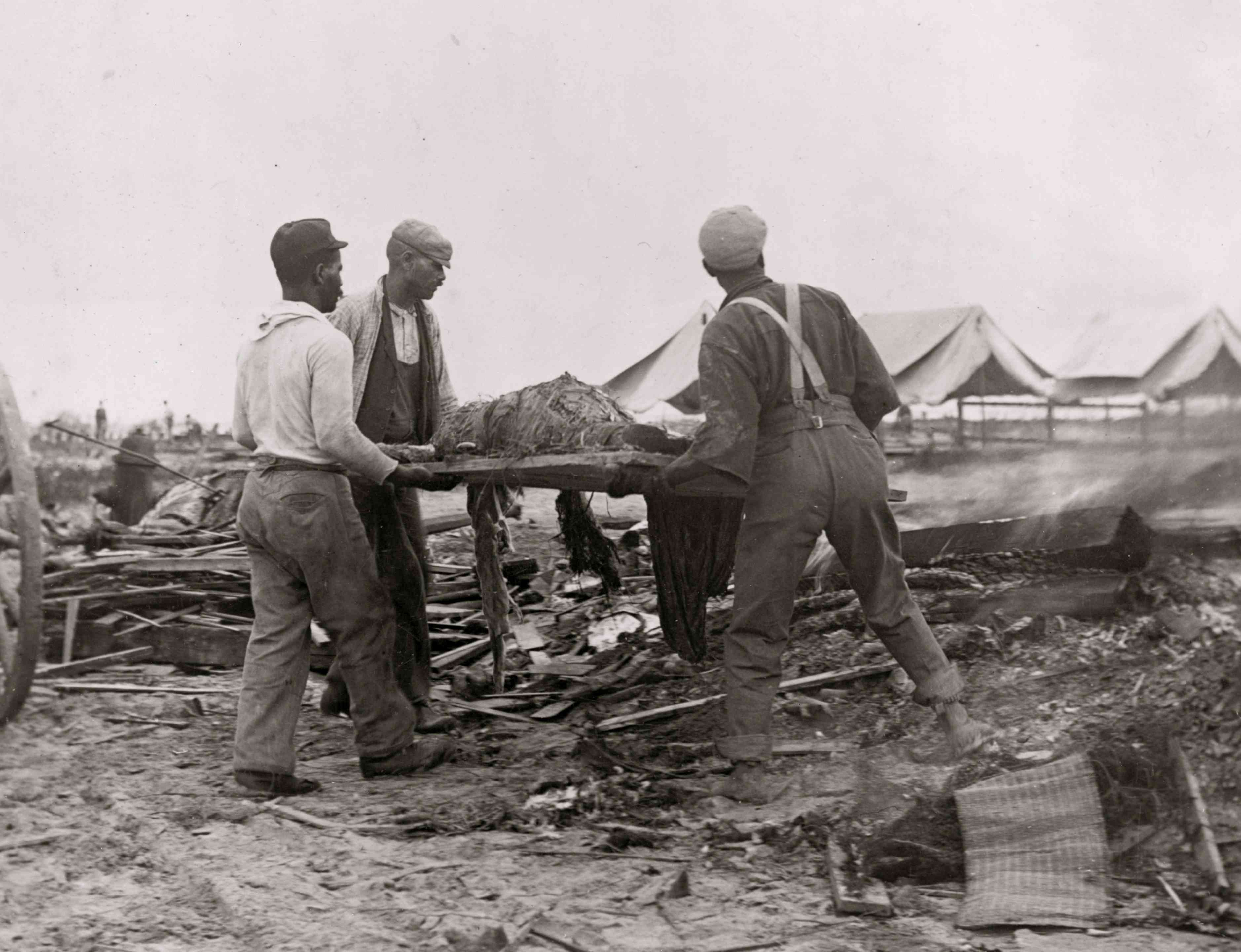 African American men carrying body on stretcher, surrounded by wreckage of the hurricane and flood, Galveston, Texas