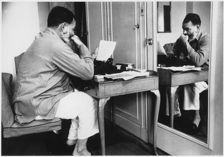Ernest Hemingway at a desk pondering his latest writing.