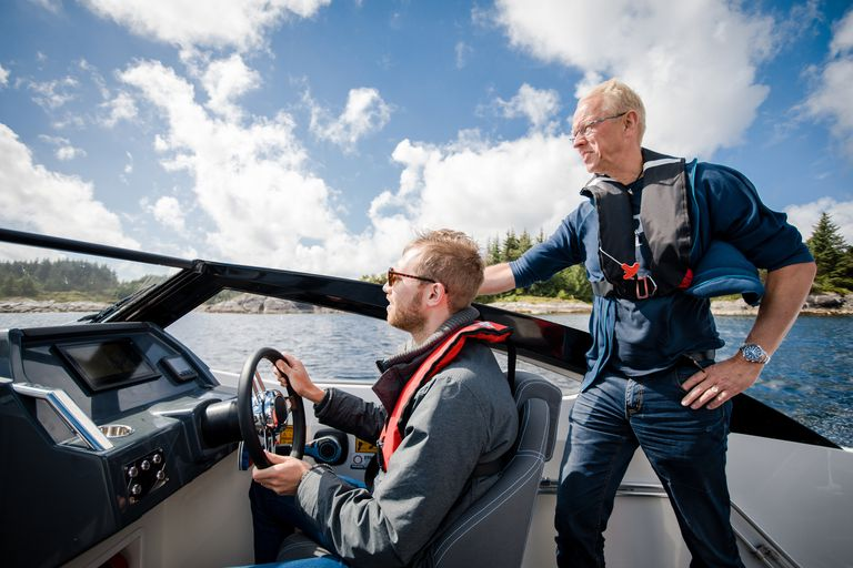 Man standing next to another man steering a boat.