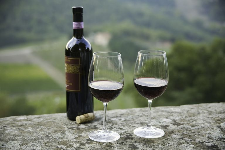 Bottle of Chianti Classico wine on top of wall with vineyards of Sangiovese grapes in background