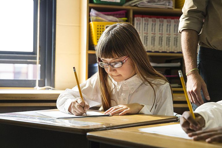 School Girl Writing Assignment with Pencil