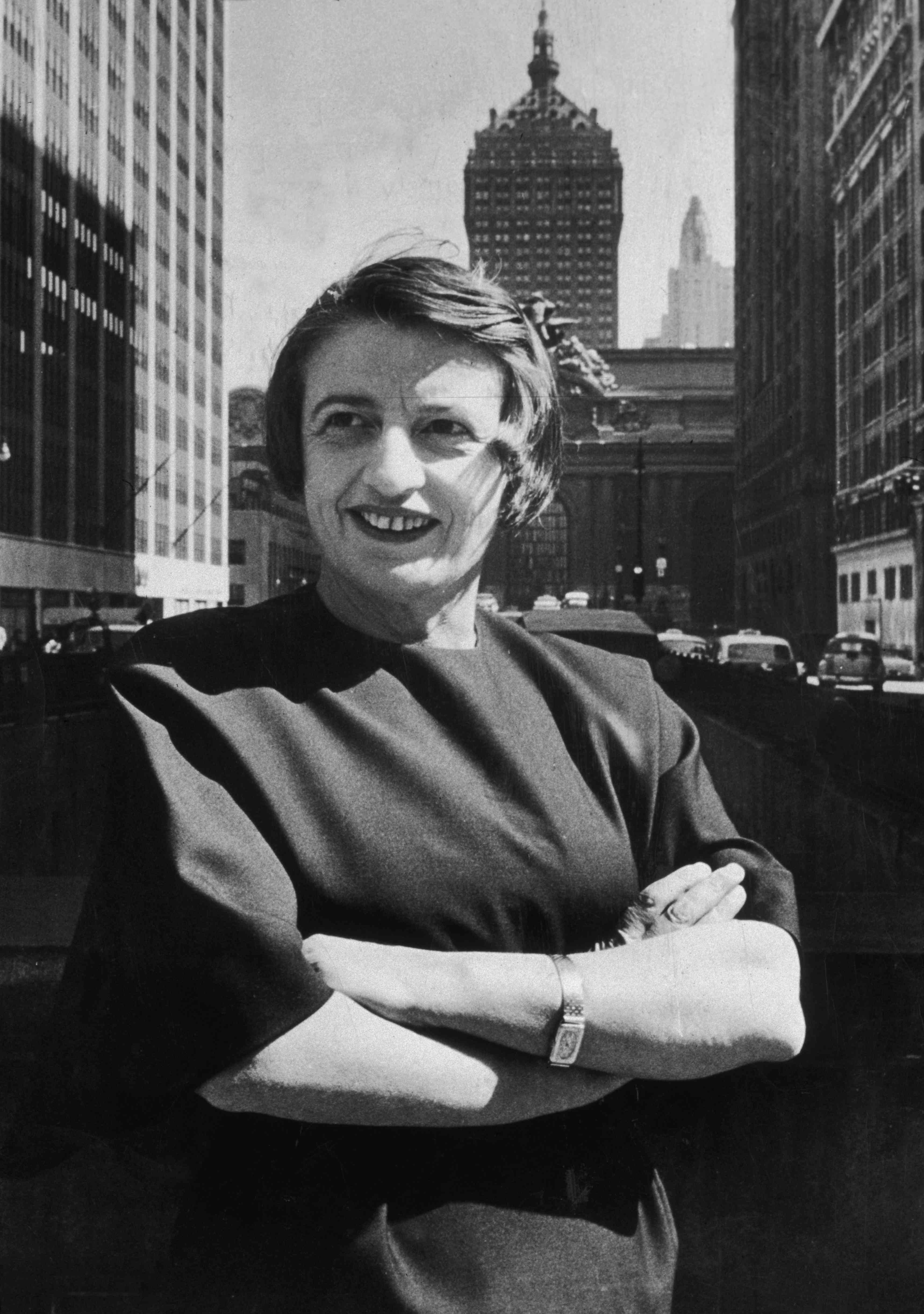 ussian-born American author and philosopher Ayn Rand, smiles and stands outdoors with her arms folded, in front of the Grand Central building, midtown Manhattan, New York City.