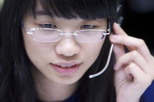 Young Chinese woman on telephone headset