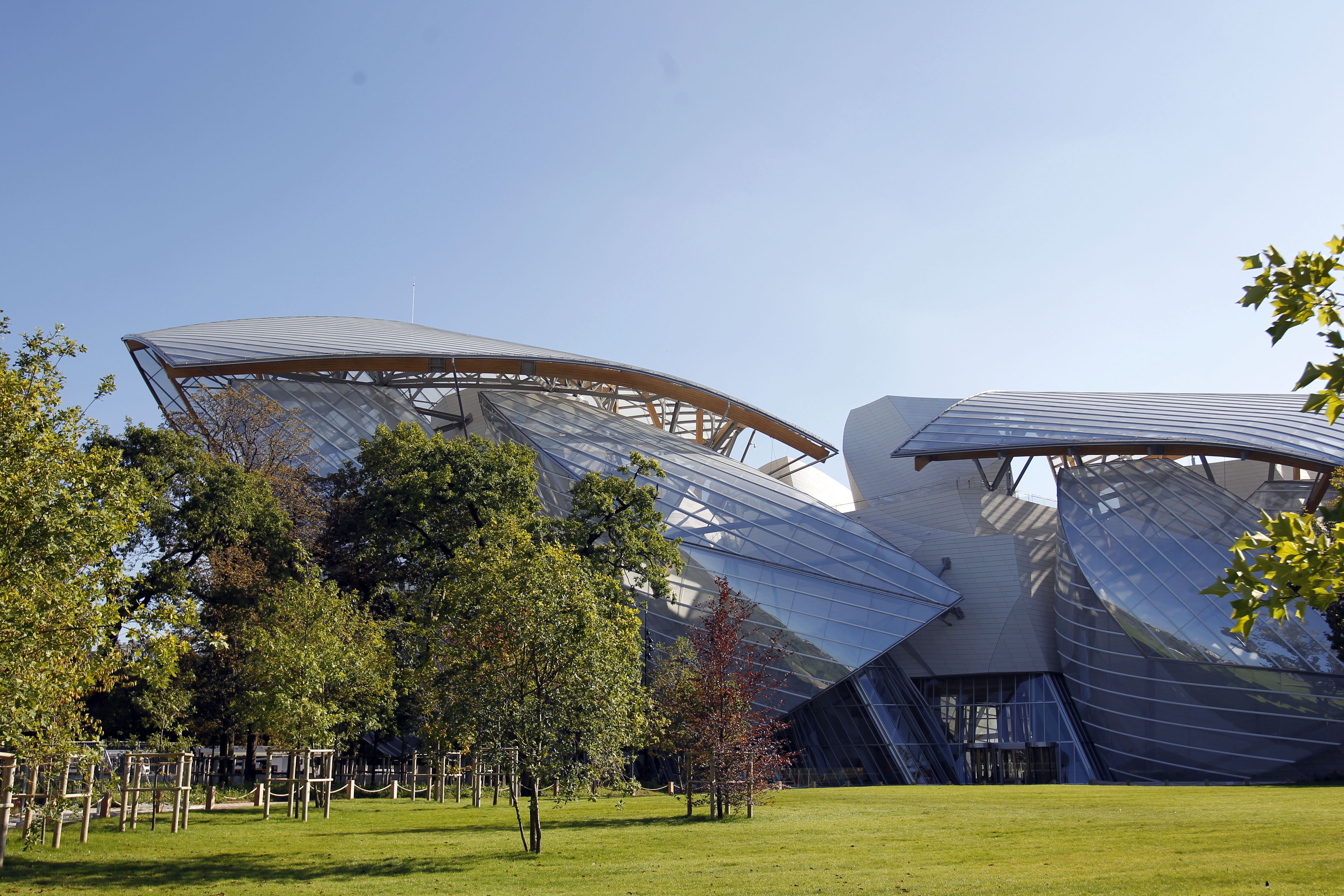 glass sails in sprawling building in a park setting