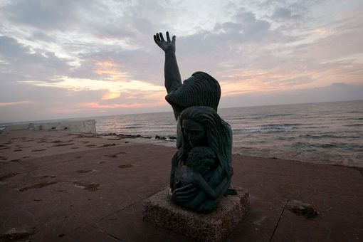 The sun rises behind the 1900 Storm Memorial in Galveston, Texas