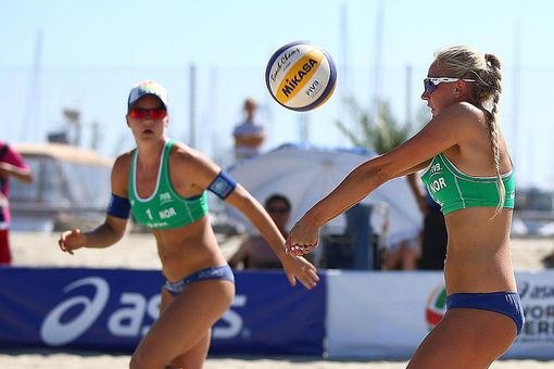 LONG BEACH, CA - JULY 23: Victoria Kjolberg of Norway (L) sets the ball for Janne Kongshavn at the ASICS World Series of Beach Volleyball - Day 2 on July 23, 2013 in Long Beach, California.