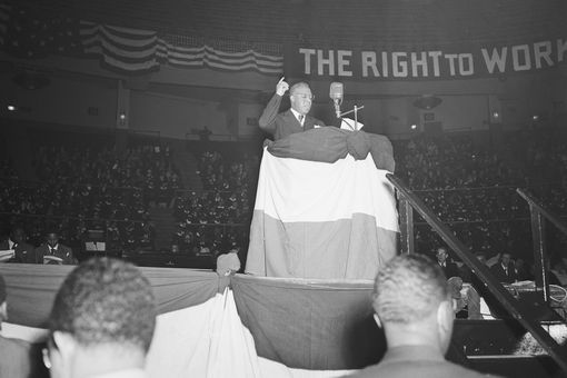 """Black and white photo of a man speaking at a podium, with a """"The Right to Work"""" banner behind him"""