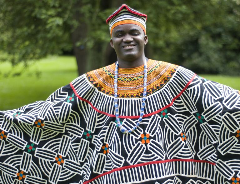 A Cameroonian man with arms spread in traditional garb.