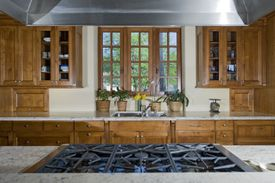 View of a kitchen with a stainless steel oven and wooden cabinets.