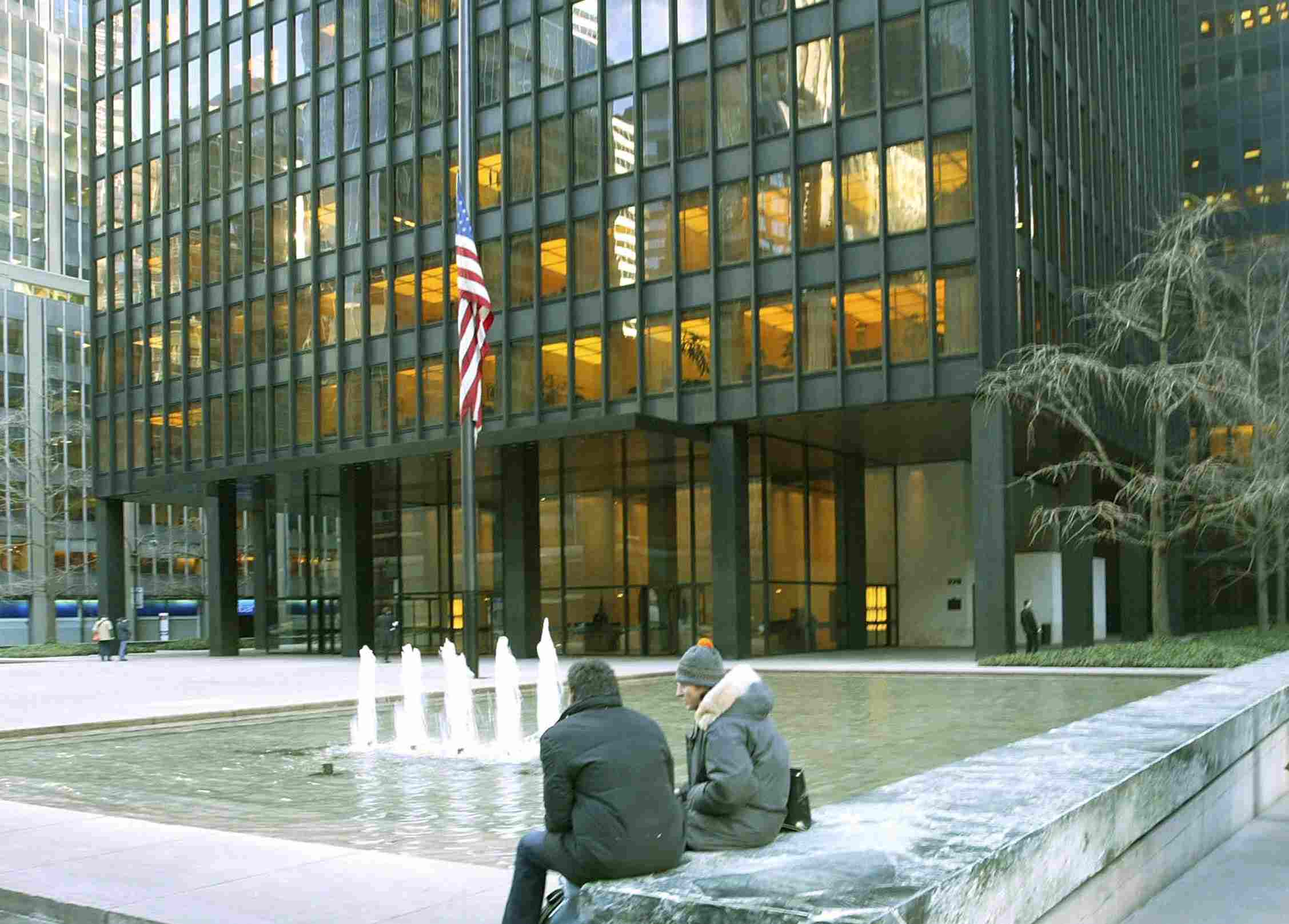 two people sitting near a pool in front of a skyscraper set back from the streets of New York City