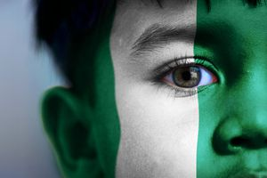 Boy with face painted like the Nigerian flag