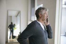 Senior man talking on cell phone, looking out window