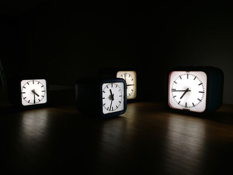 Illuminated Clock On Table Against Black Background