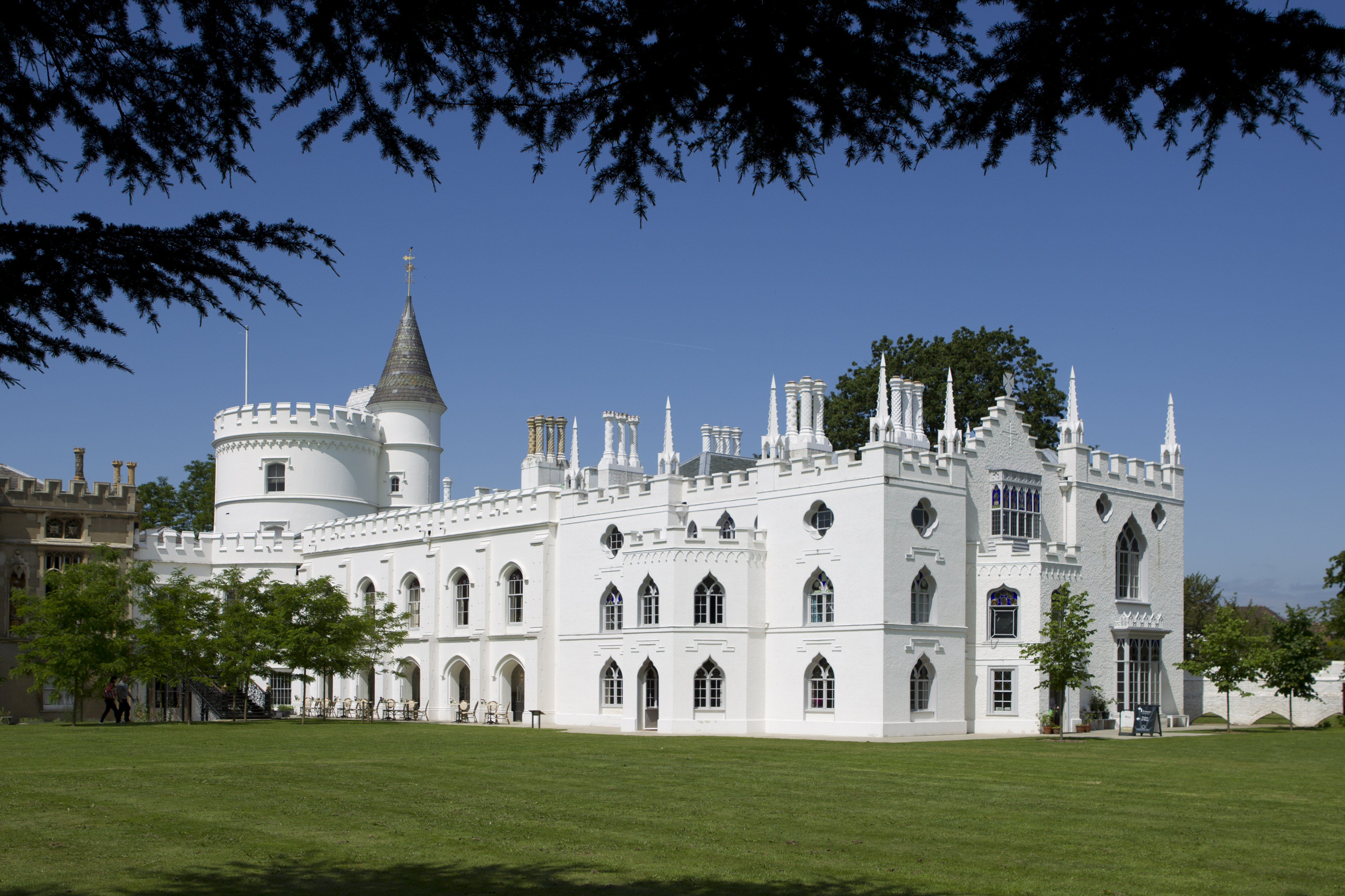 large white castle-like residence with arched windows, parapets, turrets, and crenalation