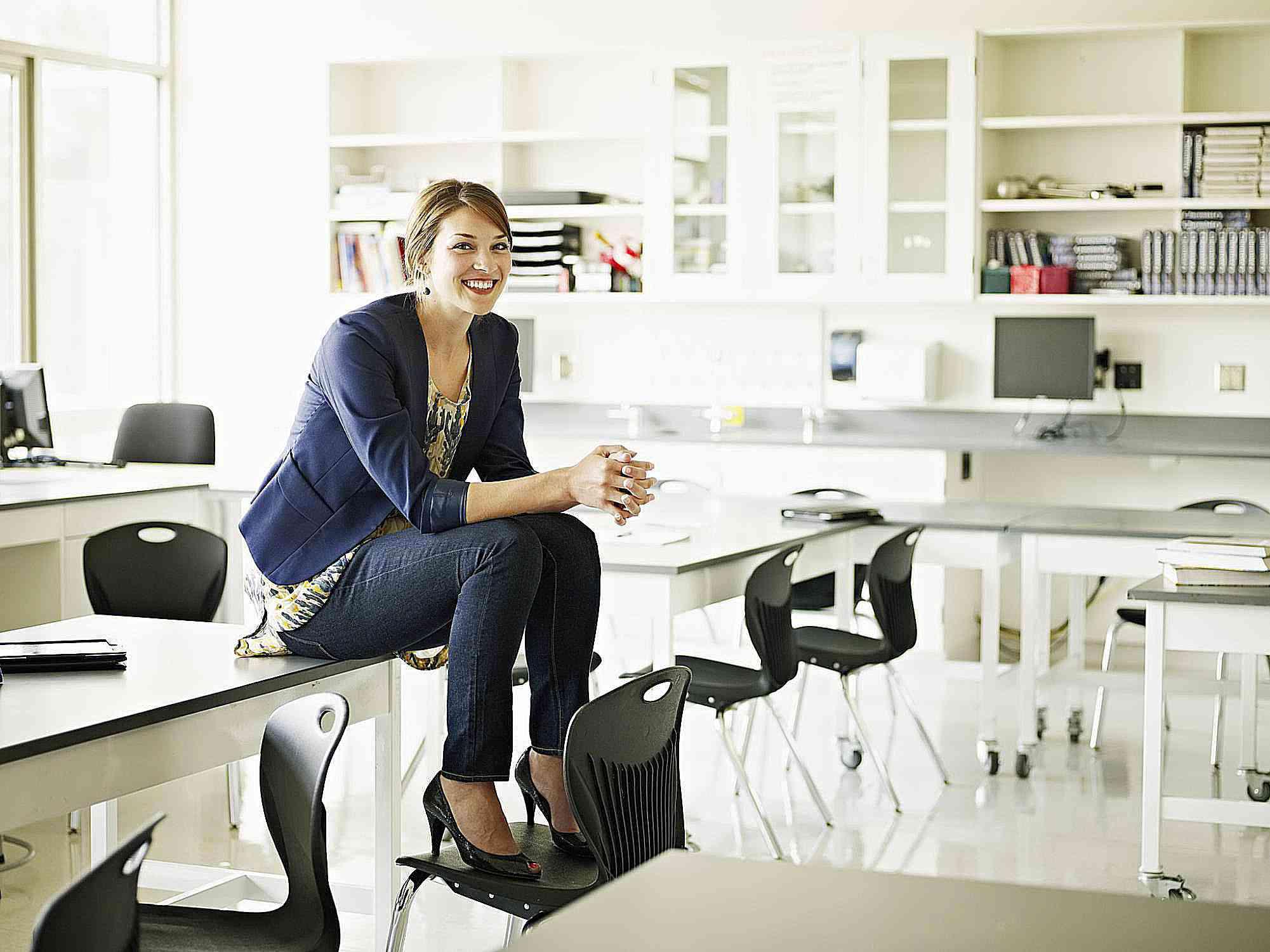 Lächelnder Lehrer, der auf Schreibtisch im Klassenzimmer sitzt
