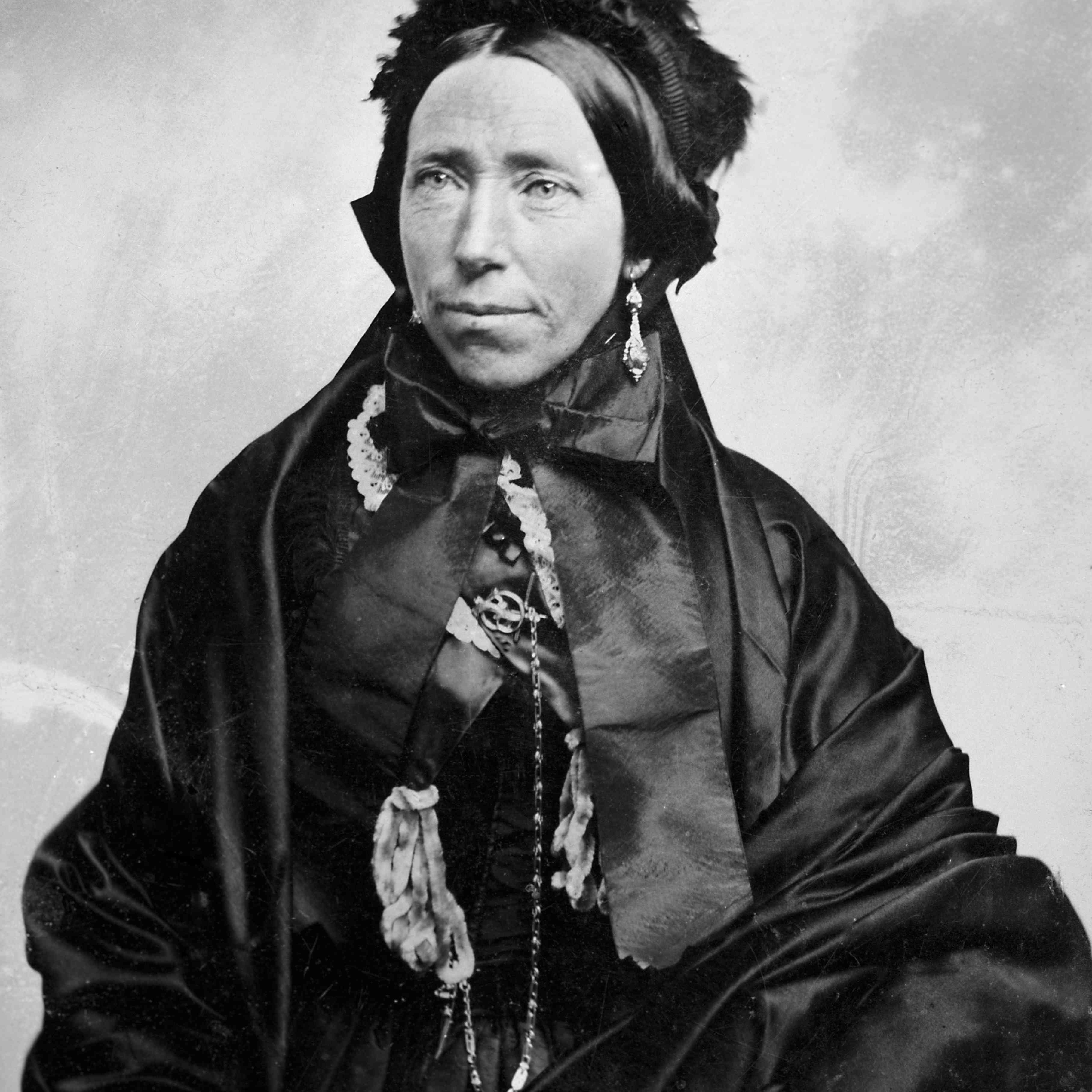 Mature woman in mourning clothes poses for tintype portrait, ca. 1880.