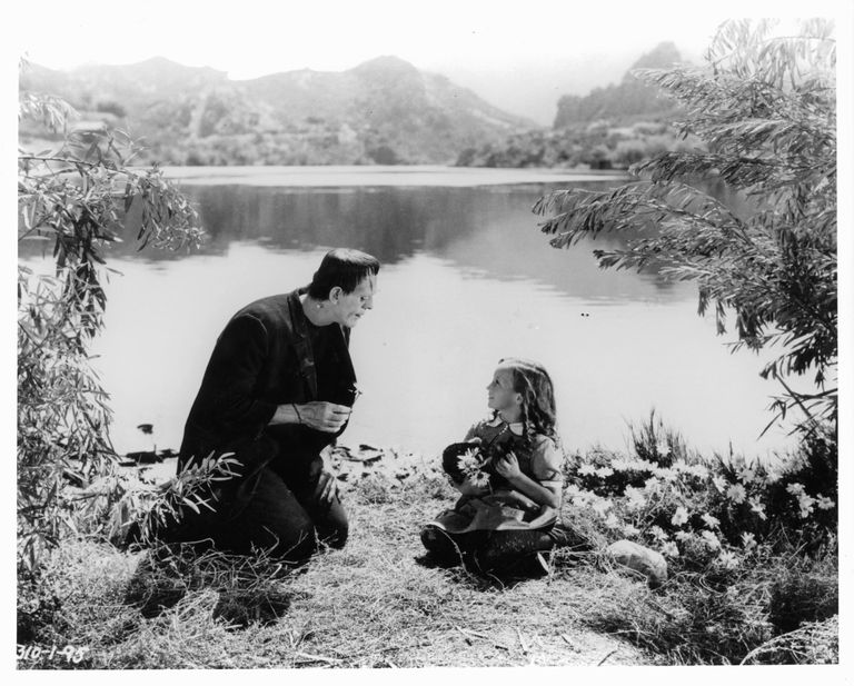 Boris Karloff as the monster sitting lakeside with little girl in a scene from the film 'Frankenstein', 1931.