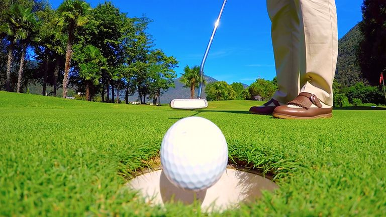 Golf ball falls into hole after being putted