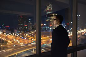 Young man looking out of window at night
