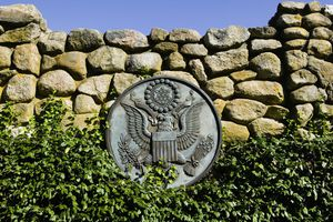 US presidential seal attached to ivy-covered stone fence