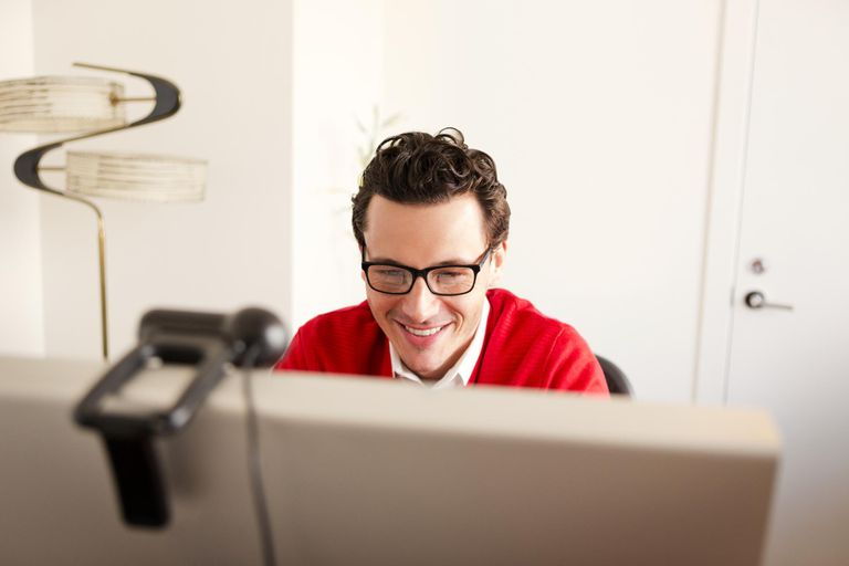 Person smiling while using a computer and livestreaming with a webcam