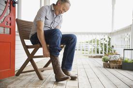 Man putting on cowboy boots