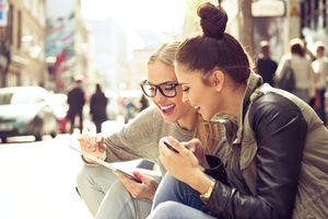 young women talking and looking at tablet