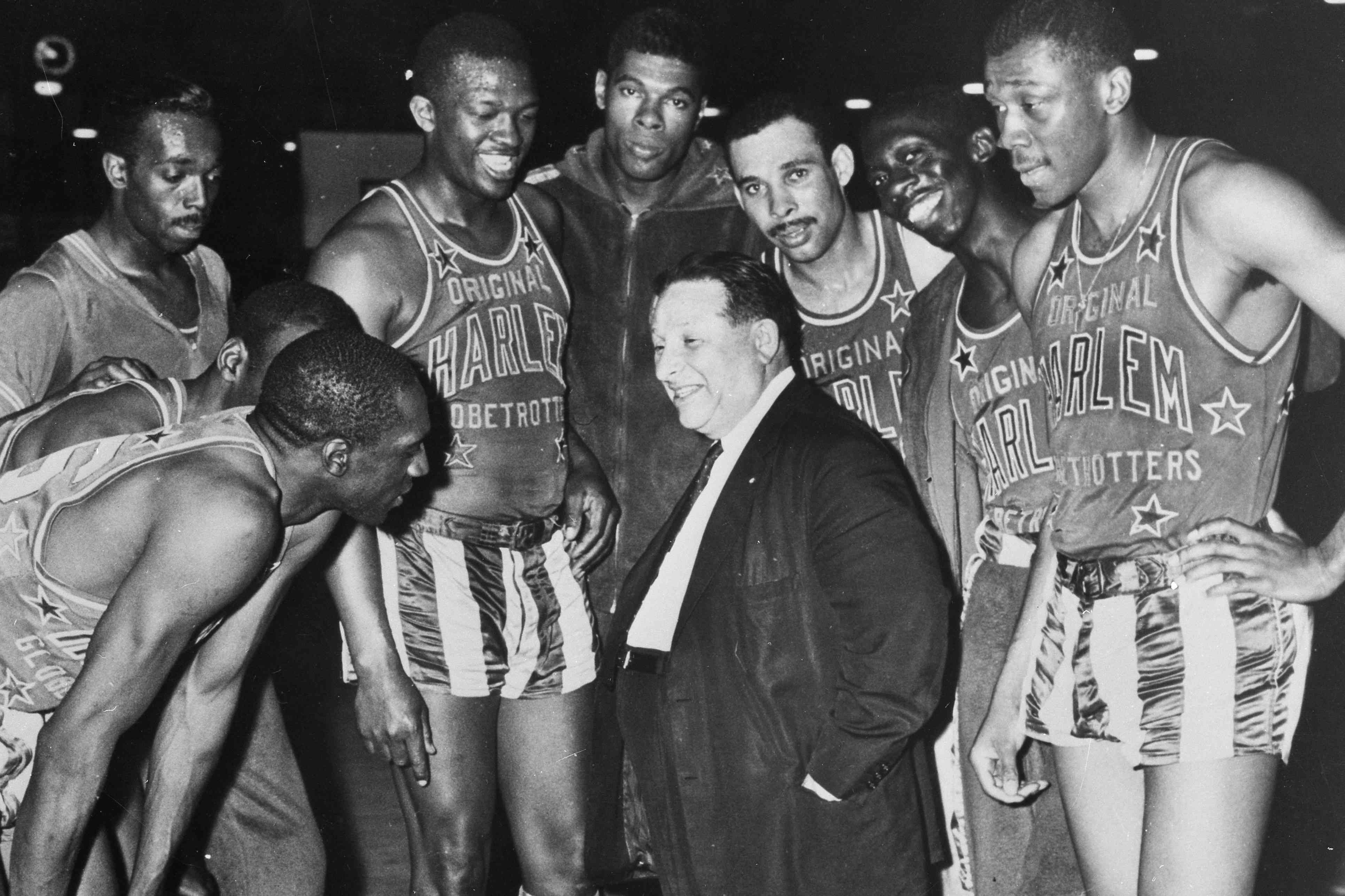 Harlem Globetrotter team members surrounding coach and owner Abe Saperstein