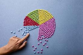 Hand pulling apart pie chart made out of small colorful balls