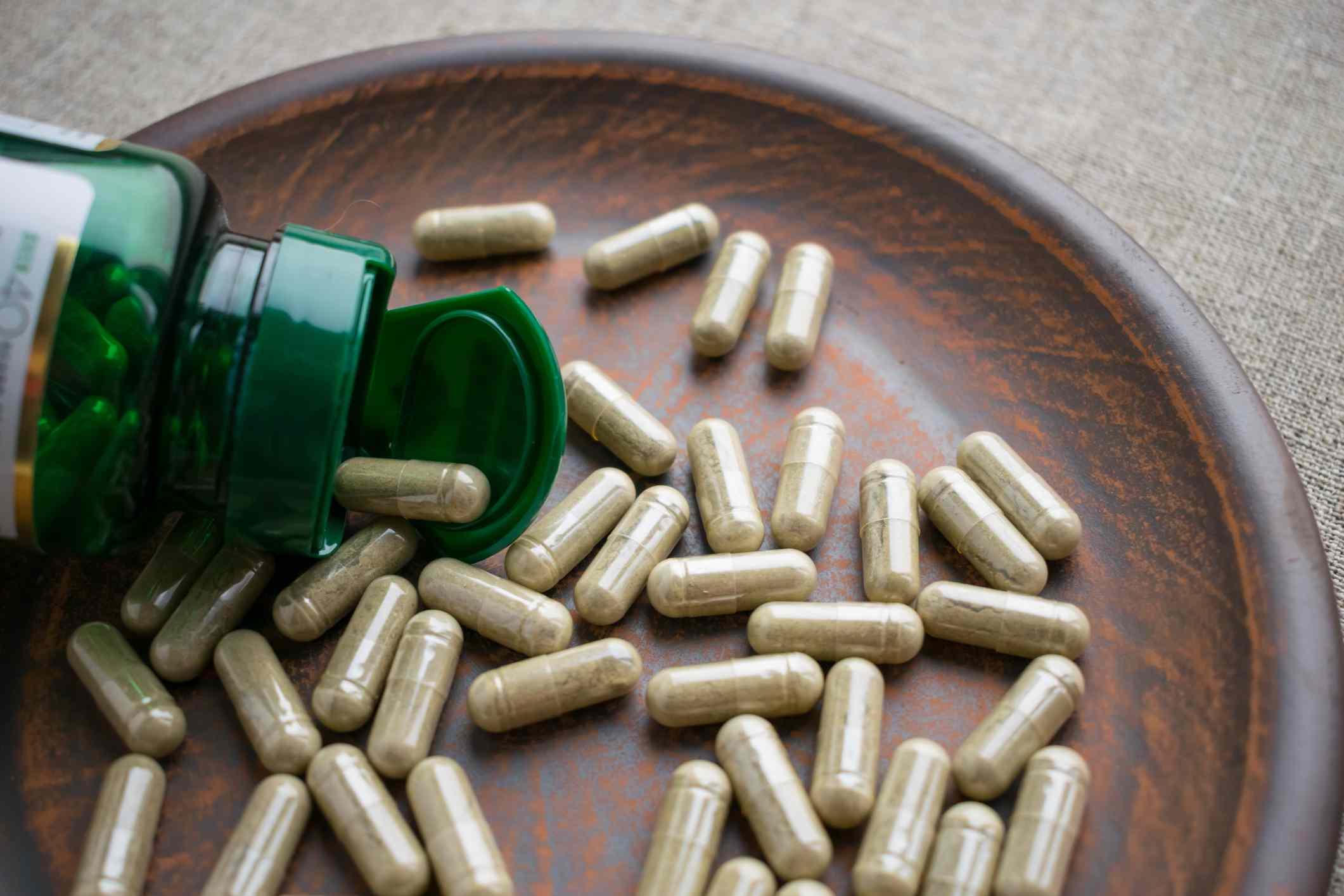 Close up of a biotin bottle spilling pills