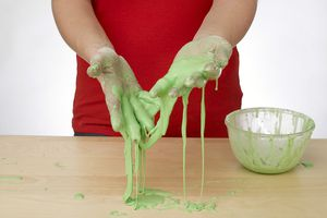 Person making slime with hands covered standing over a wooden table.
