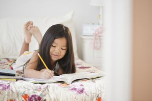 Korean girl doing homework on bed