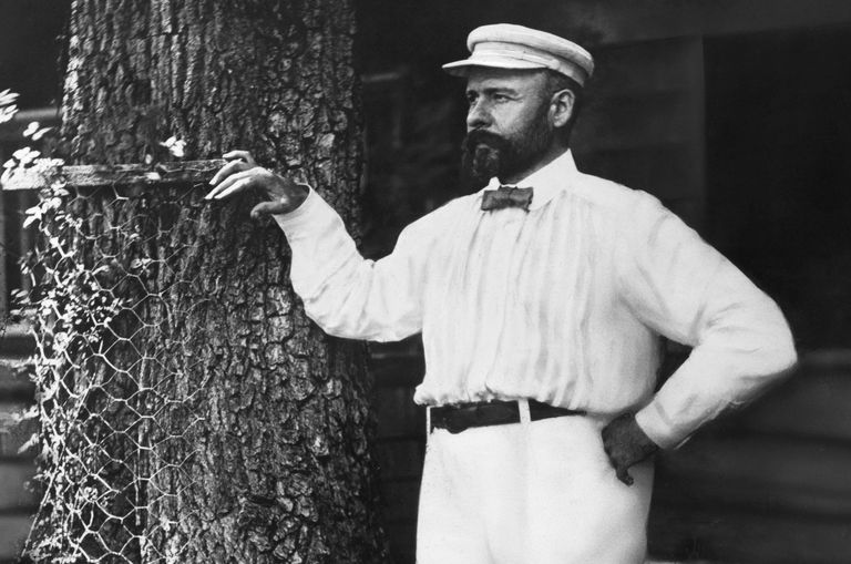 Black and white photo of bearded Louis Sullivan, dressed in white pants, shirt, and hat, bow tie, standing and leaning on a tree