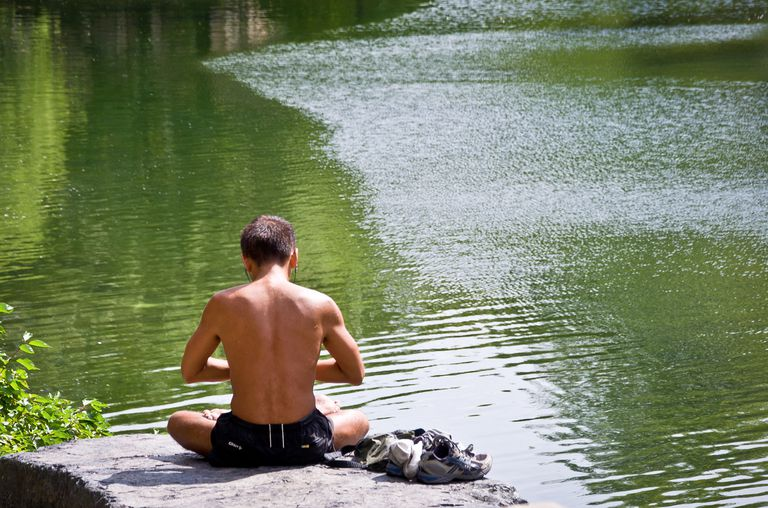 Man meditating by a body of water