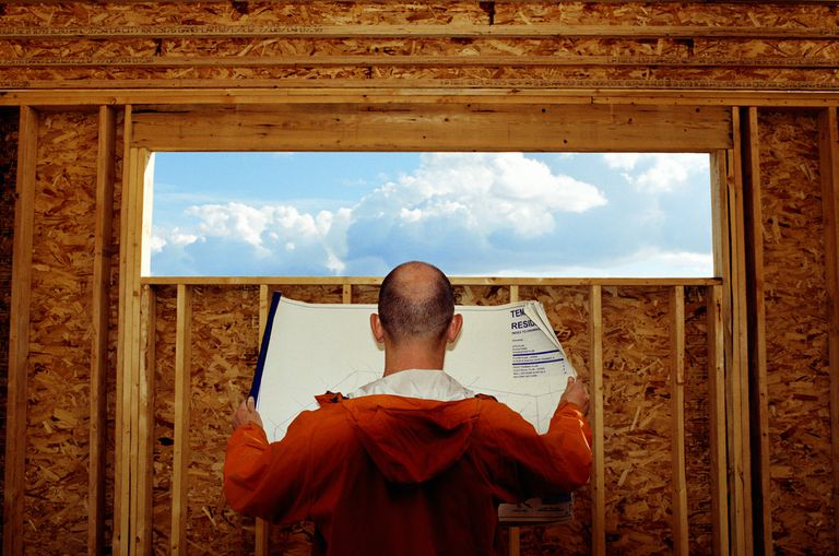 back of man reading blueprints in front of a wide and narrow opening in a wall