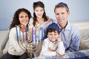 A family celebrates the eighth day of Hanukkah with all candles lit on the menorah