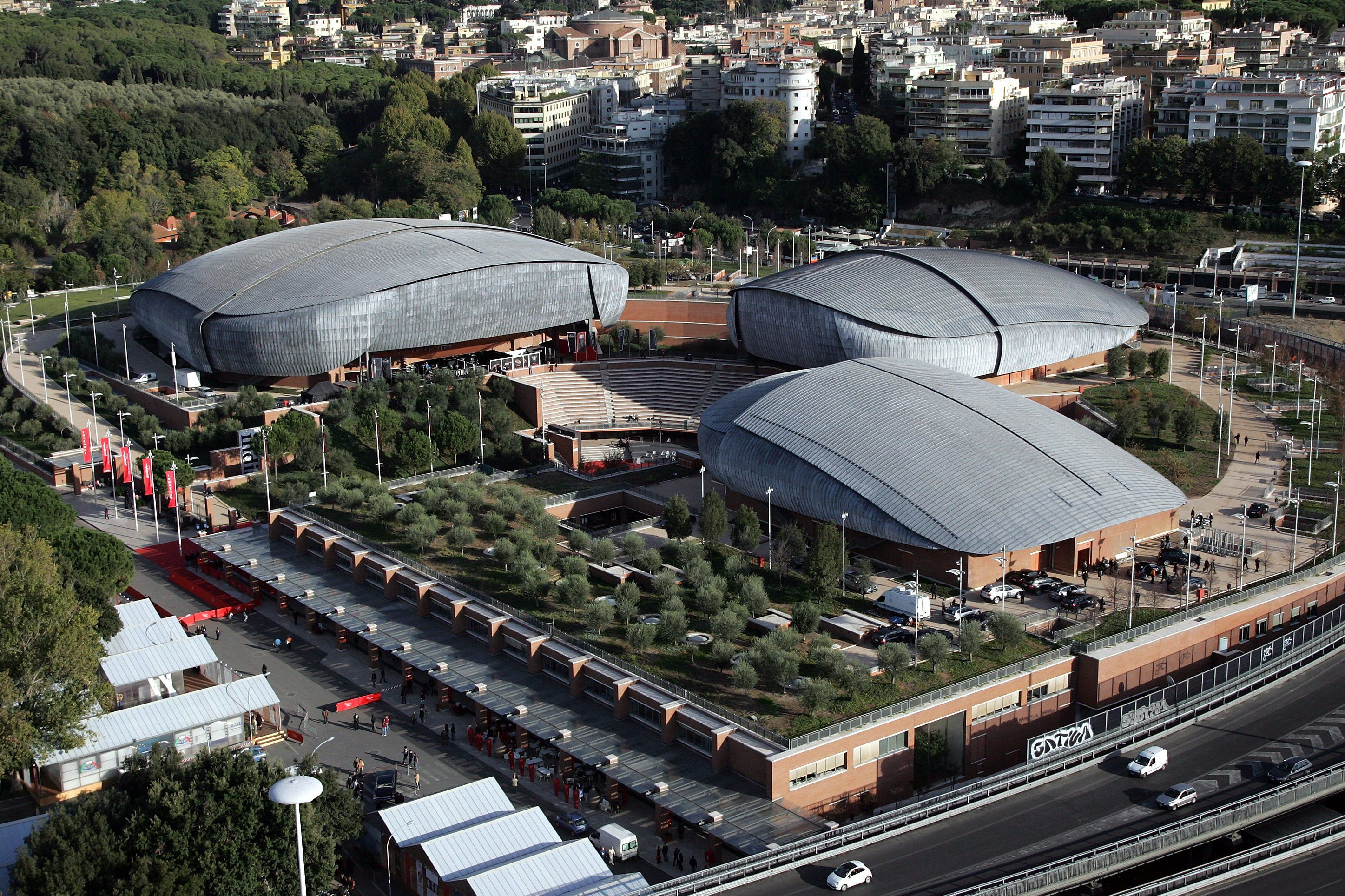 aerial view of three large, asymmetrical blob-like buildings surrounding an amphitheater