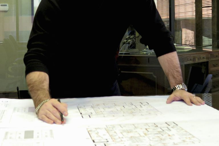 Cropped photo of male architect's arms and hands on a large blueprint, man dressed in black holding a pen, large silver watch
