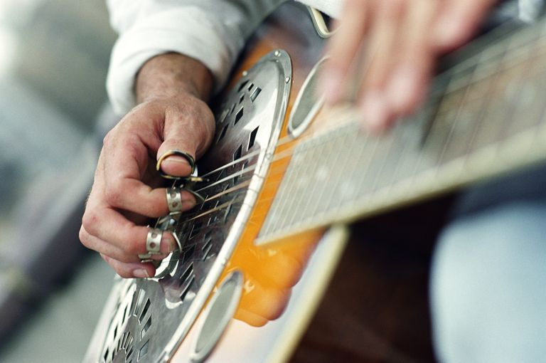 Man playing guitar, focus on hands