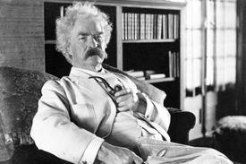 Mark Twain sitting in a chair