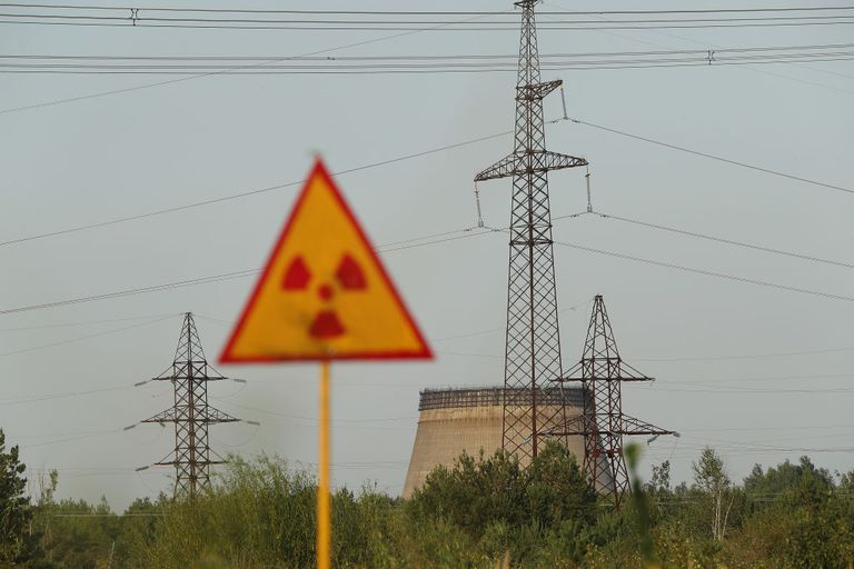 A radiation sign and a partially-constructed and abandoned cooling tower at Chernobyl nuclear power plant