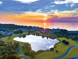 A colorful sunset over water with an aerial view of campus and a lake surrounded by green grass
