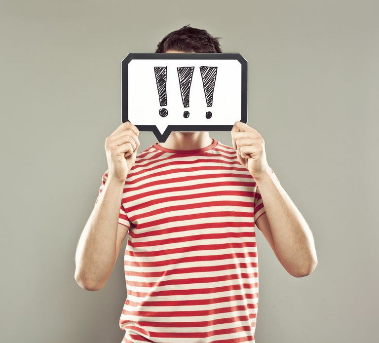 Young man holding speech bubble with exclamation marks