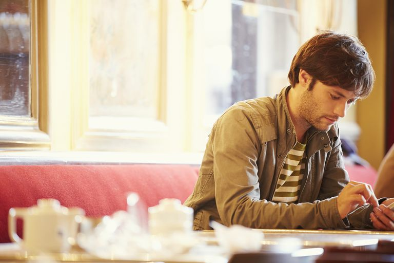 Man using phone in cafe